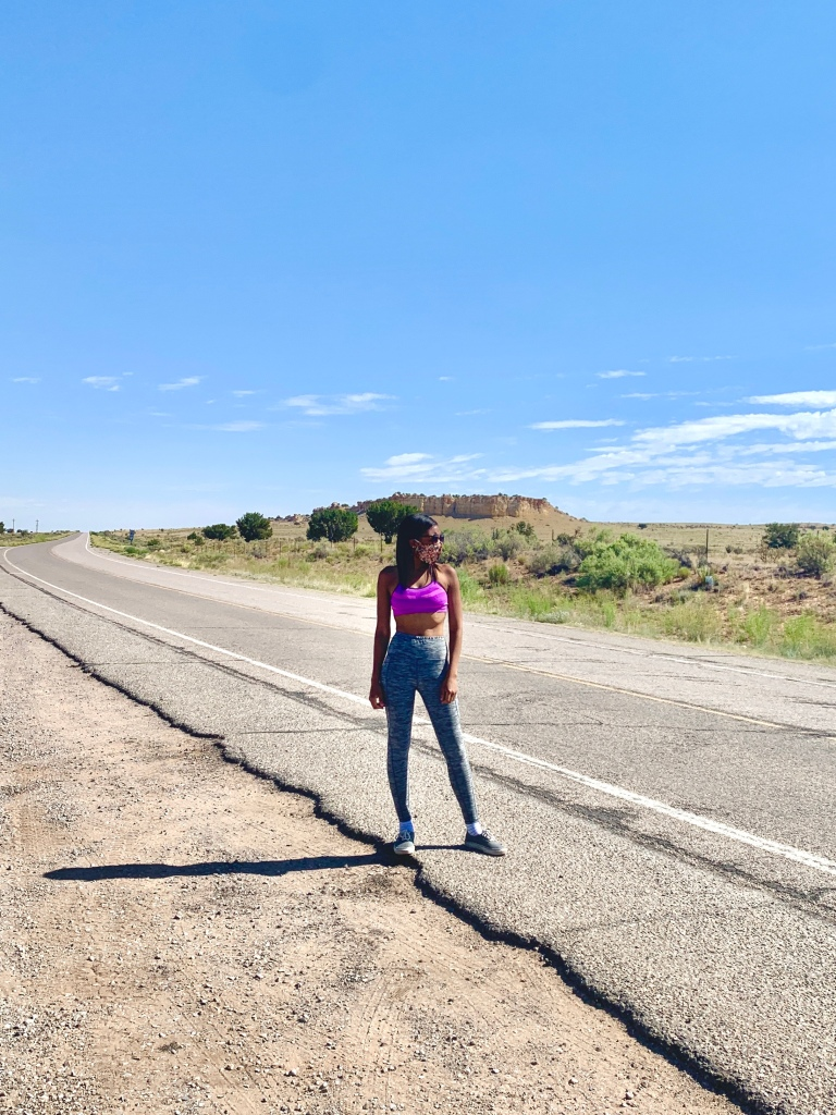 Jasmine standing in the middle of a dusty desert road. She wears a mask and sun glasses and stares off camera.