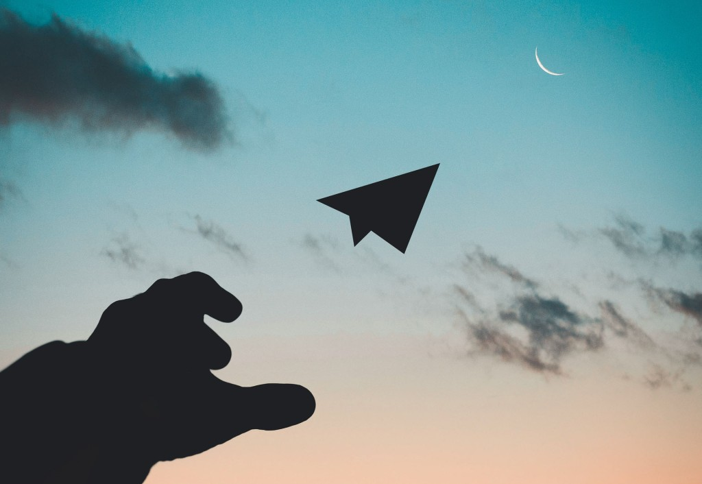 Silhouette photo of man throwing a paper plane in front of a sunset.