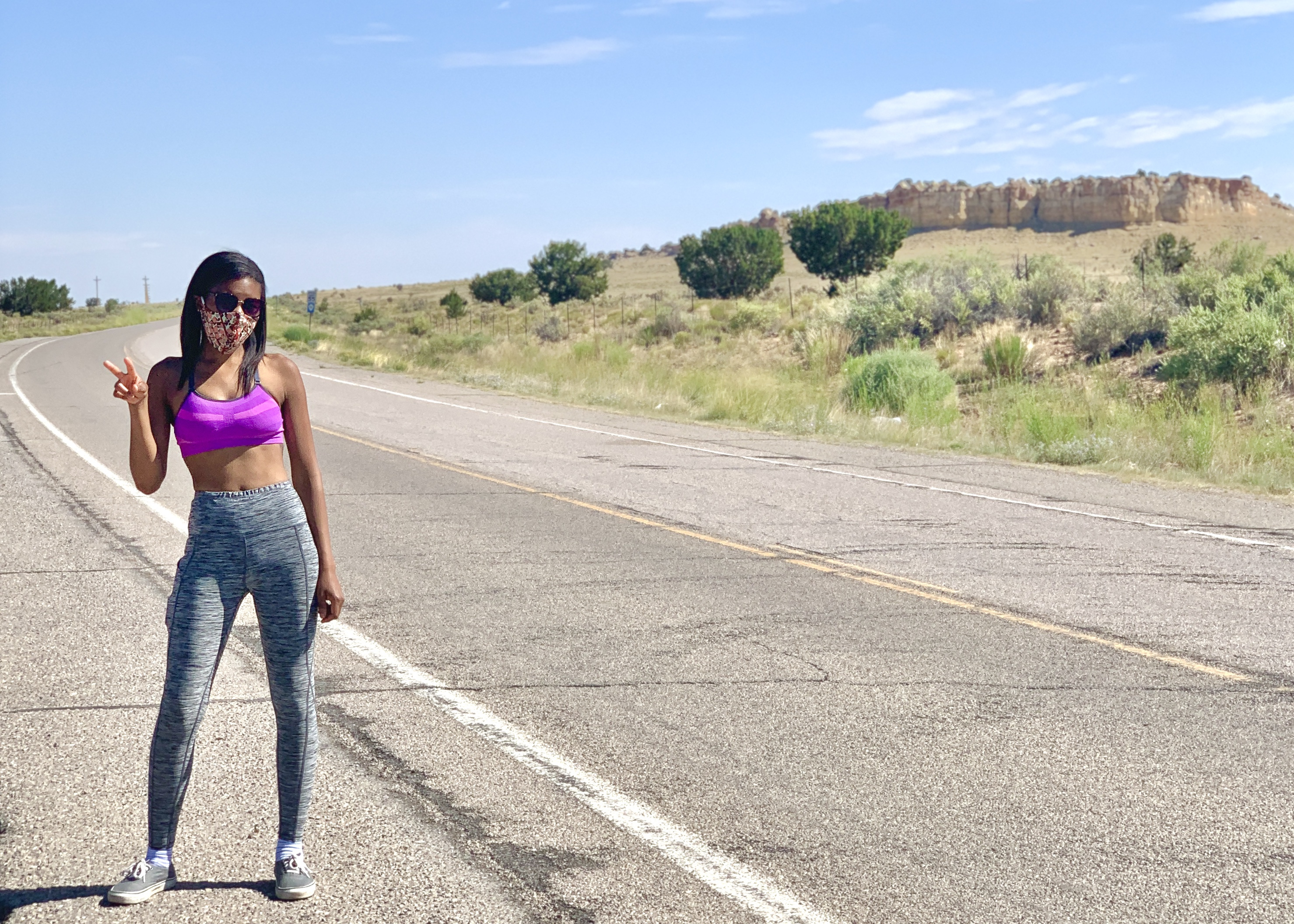 Jasmine wears a mask sunglasses and workout gear. She stands in the middle of an empty road flashing a peace sign.
